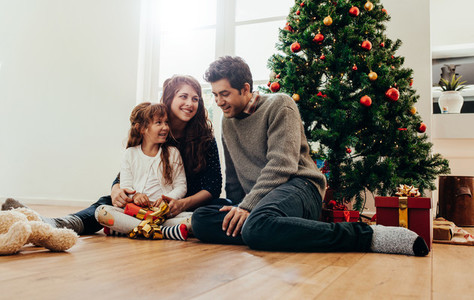 Small happy family celebrating Christmas at home