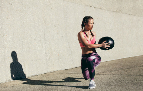 Sportswoman stretching with medicine ball