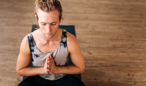 Fitness guy doing yoga meditation
