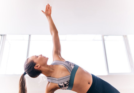 Fit woman doing the side plank yoga pose
