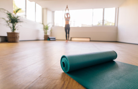 Exercise mat on floor with woman doing yoga