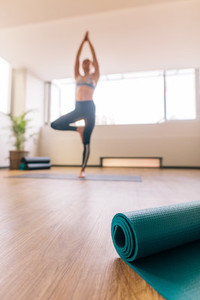 Yoga mat in fitness center with woman meditating at back