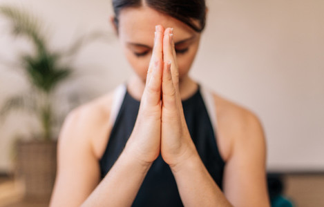 Woman in namaste yoga pose meditating
