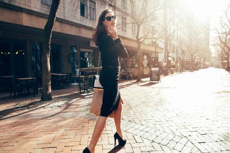 Fashionable female using phone outdoors