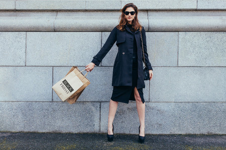 Stylish woman against wall with shopping bags