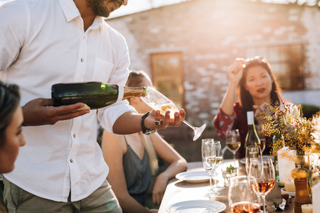 Man serving champagne to friends during party