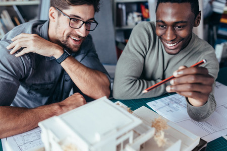 Two architects working on a building model