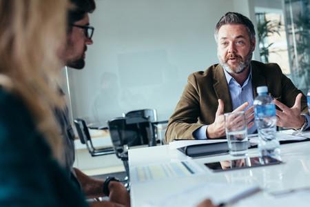 Businessman explaining new business ideas to peers