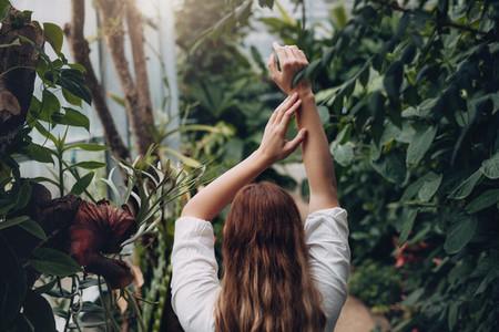 Female model standing inside plant nursery