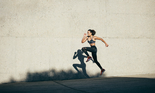 Healthy woman running and jumping outdoors