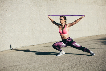 Strong woman exercising with resistance band
