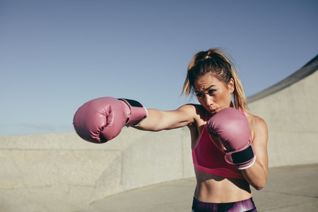Sportswoman training boxing outdoors