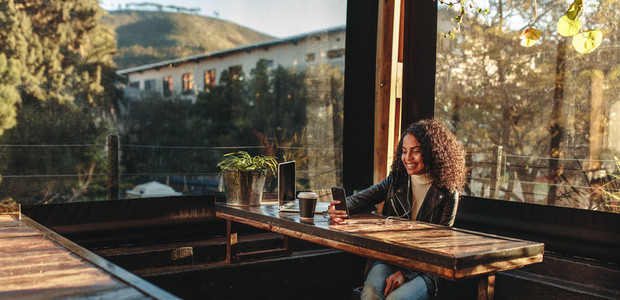 Woman sitting in a coffee shop looking at mobile phone