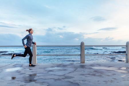 Female runner running on seaside promenade