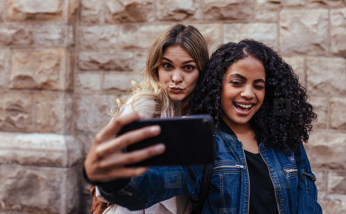 Two women posing for a selfie outdoors