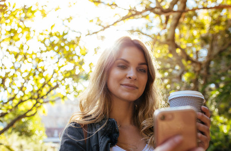 Woman clicking a selfie holding a coffee glass