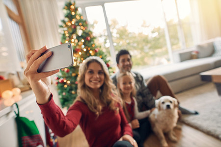 Happy family taking self portrait during Christmas at home