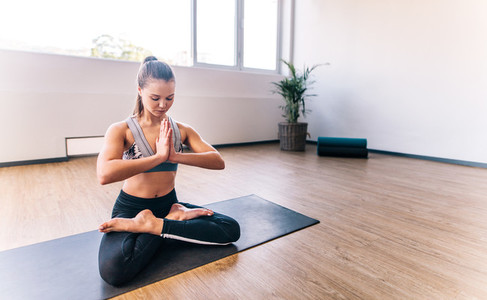 Fit woman keeping fit by doing yoga