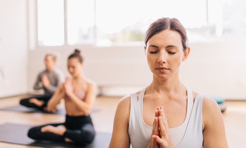 Healthy woman doing meditating in yoga class