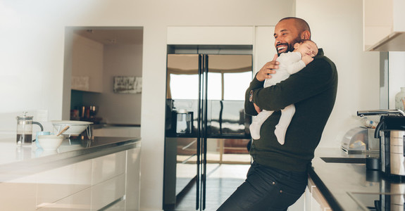 Happy father with son sleeping in his arms in kitchen