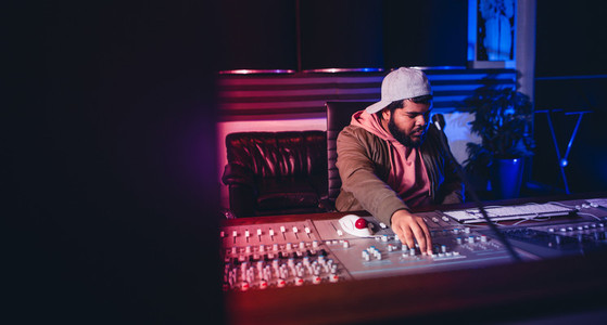 Engineer working on sound mixing desk in recording studio