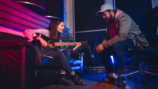 Man and woman composing a song on the guitar