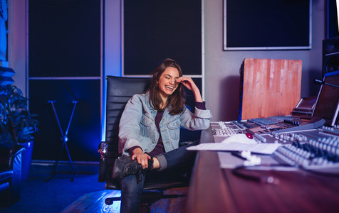 Smiling female sound technician in recording studio