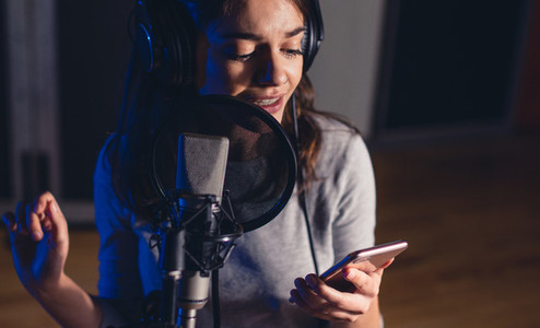 Singer singing in the recording studio with mobile phone