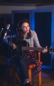 Female singer recording in professional music studio