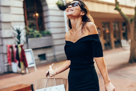 Asian woman with shopping bags enjoying on city street
