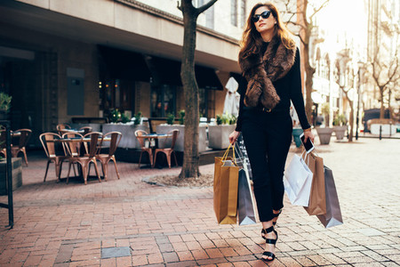 Stylish woman on city street with shopping bags