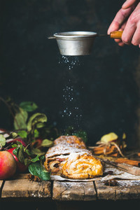 Man039s hands sprinkling sugar powder on apple strudel cake