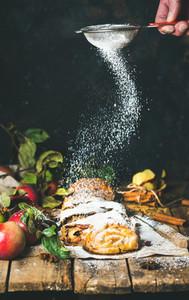 Man s hand with sieve sprinkling sugar powder on apple strudel