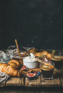 Breakfast with croissants ricotta prosciutto coffee and berries copy space