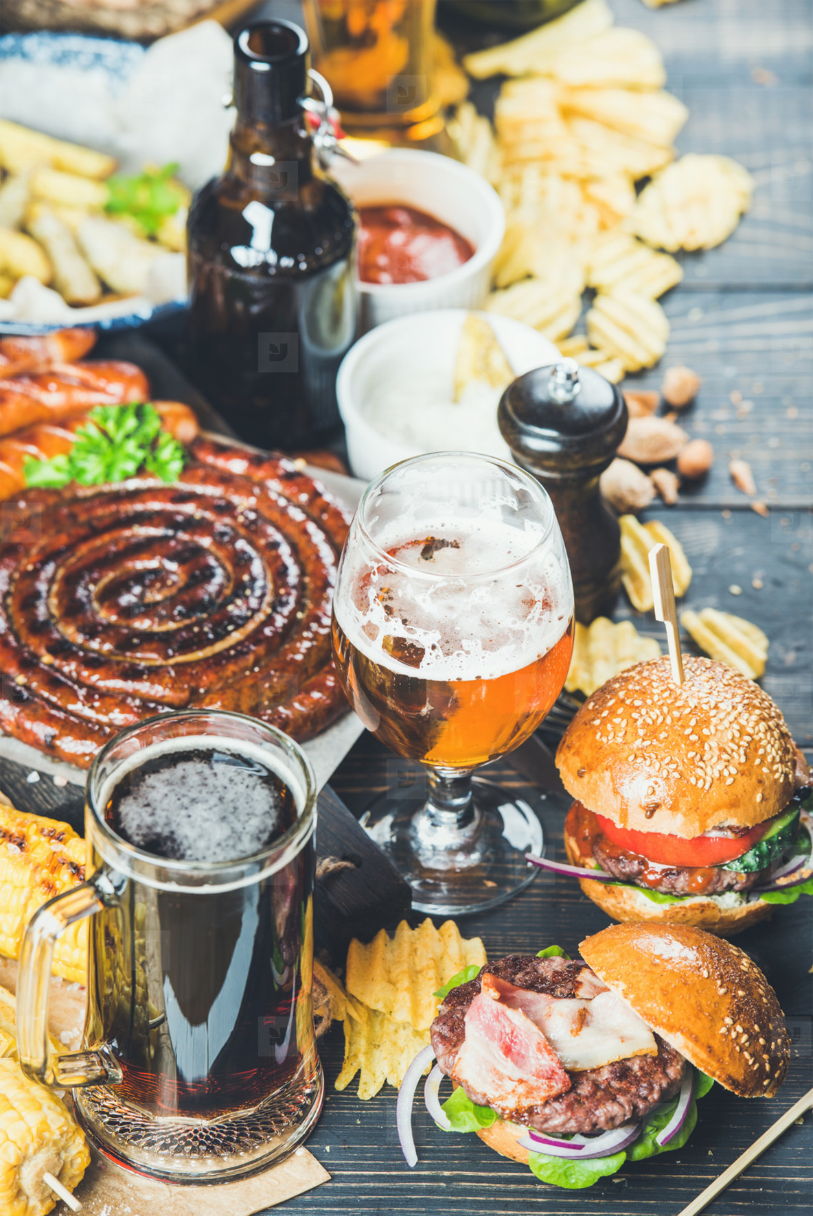 Beer and snack set on dark wooden scorched background
