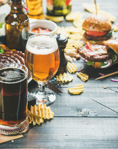 Beer and snack variety on dark wooden scorched background