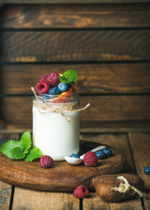 White yogurt with fresh berries  peach and mint leaves