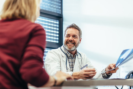 Happy doctor talking with patient in his office