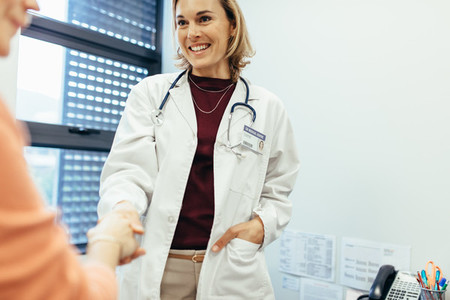 Female physician shaking hands with her patient
