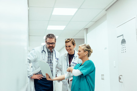 Team of medics looking at medical report in hospital corridor