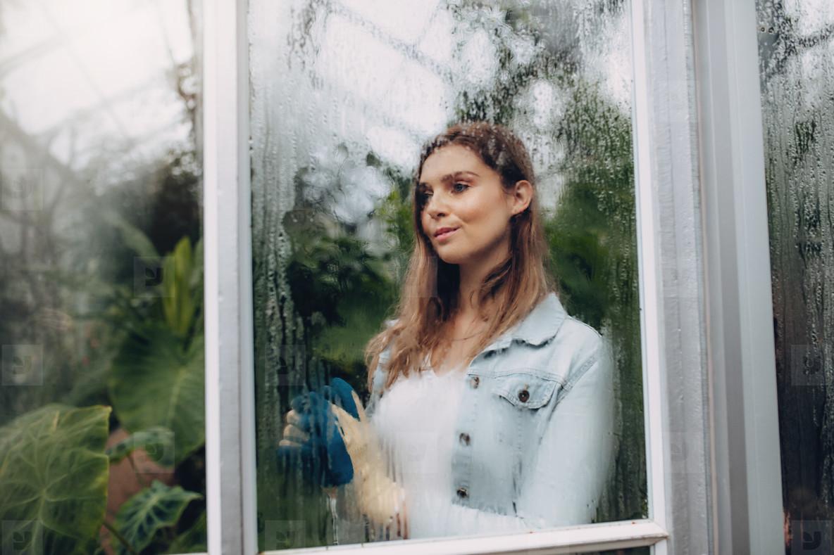 Female standing inside greenhouse