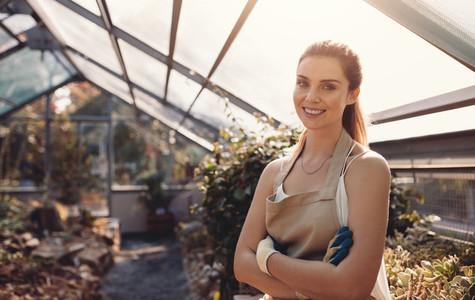 Confident female gardener at plant nursery