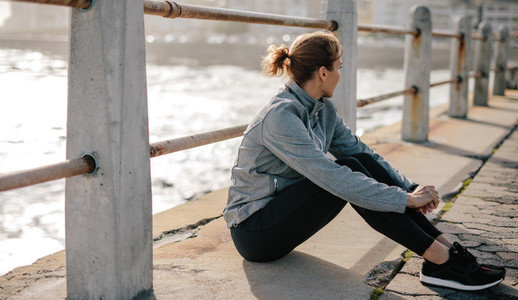 Woman relaxing at seaside promenade after workout