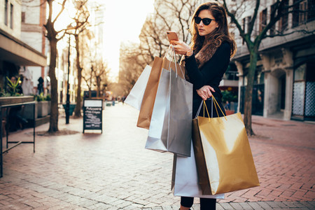 Woman using a smart phone while shopping in the city
