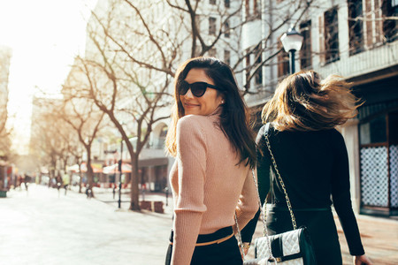 Asian woman walking with her friend on street