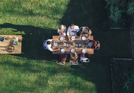 Friends enjoying meal at outdoor party in backyard