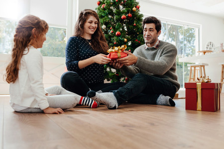 Young couple celebrating Christmas with their daughter
