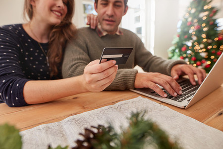 Couple shopping online for christmas with credit card and laptop