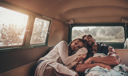Couple on roadtrip sleeping together in van
