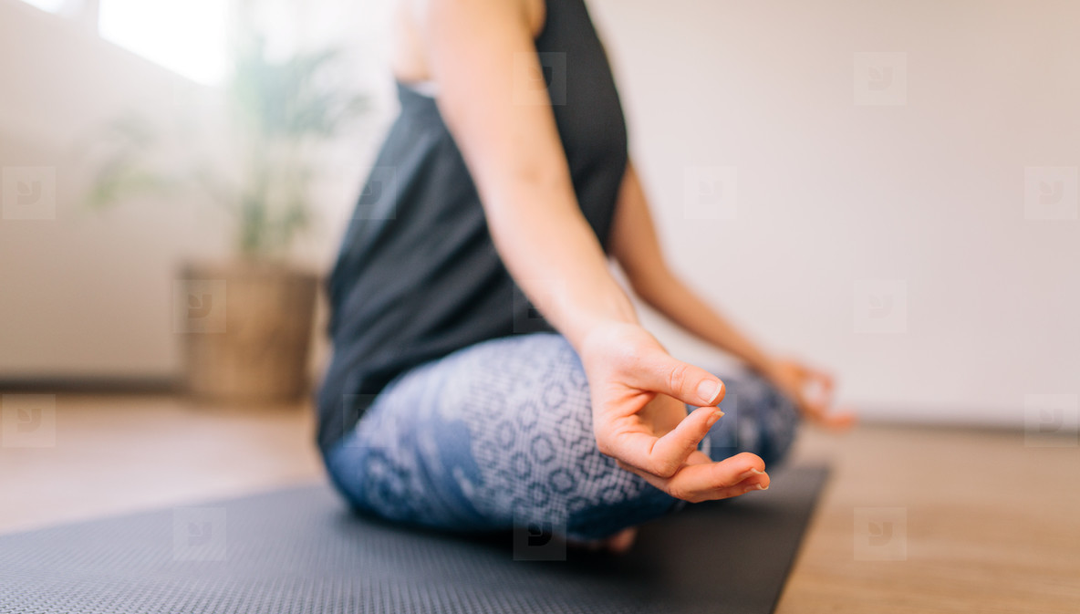 Woman in lotus yoga pose indoors